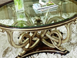 Bossa Nova Cocktail Table shown with:Contemporary HavanafinishVersailles Leaf finishtrimDecorative metalwork with ball detail in Versailles finishClear inset glasswith beveled edge