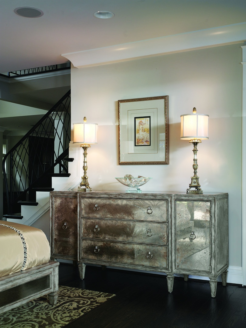 Design Folio Credenza/Dressershown with:Silver CloudfinishTransparent Antique Mirror over fabric on doors, drawers,side panels, and topTransitional LegCrystal Ring decorative hardware in Polished Nickel finish