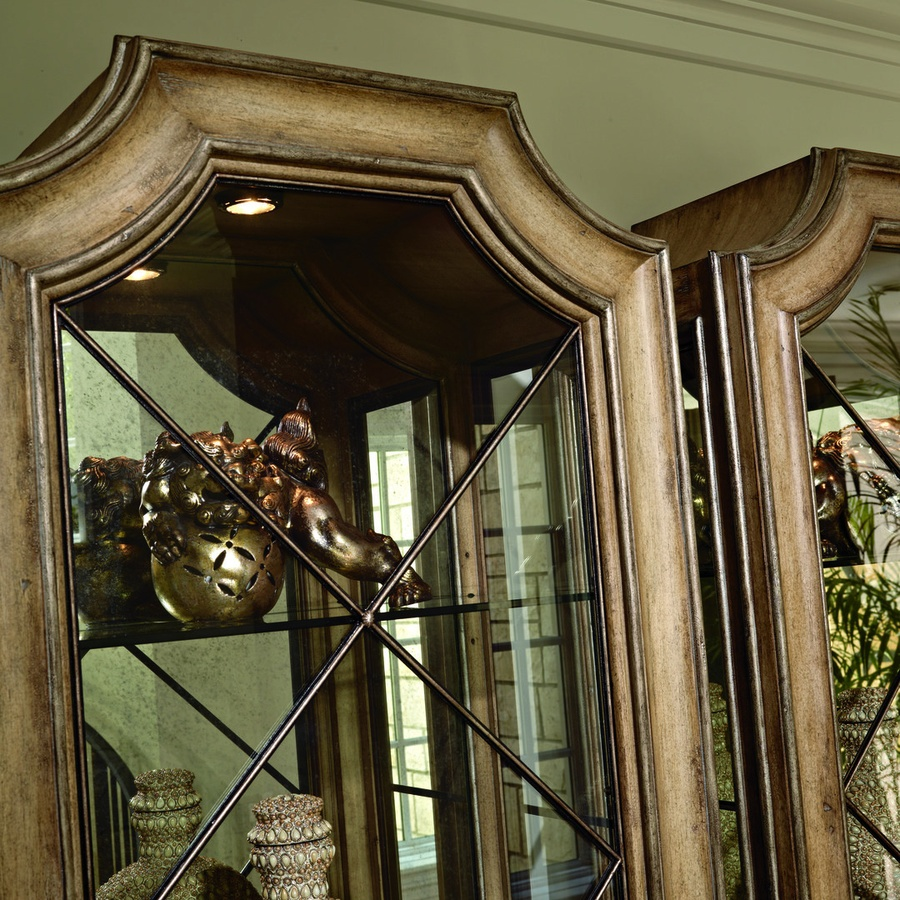 Rivoli Display Cabinet shown with:Heirloom Desert finishAged Silver Cloud Leaf finish trimDecorative metalwork in signature finish withSilver Cloud Leaf finish trimAntique Mirror back