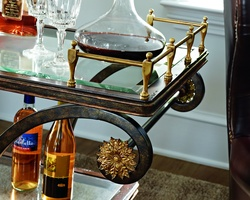 Rivoli Serving Cart shown with:Heirloom Brentwood finishAged Gold Leaf finish trimDecorative metalwork in Aged Metal finish withAged Gold Leaf trimInset clear glass top and shelf with beveled edgeAntique Brass gallery and wheels