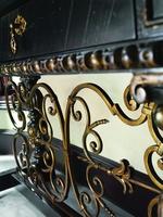 SevilleConsoleshown with:Old World Vintage NoirfinishAged GoldLeaf finish trimDecorative metalwork inAntique GoldfinishPolished Madeira Marble top