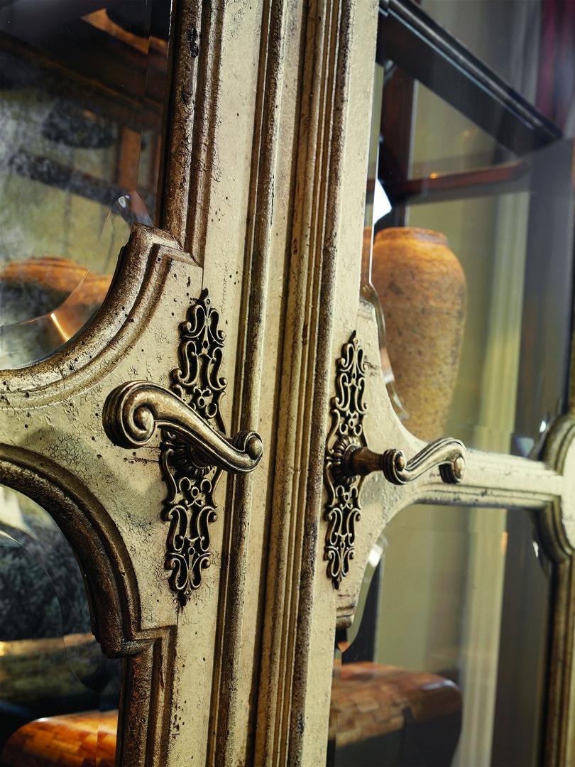 Seville Display Cabinet shown with:Old World Vintage Noir finishAged Gold Leaf finish trimContrast interior in Heirloom Brentwood finishDecorative metalwork in Antique Gold finishAntique Brass hardware