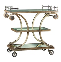 Rivoli Serving Cart shown with:Versailles finish on base and decorative metalworkAntique Mirror on platform baseInset clear glass top and shelf with beveled edgeAntique Nickel gallery and wheels