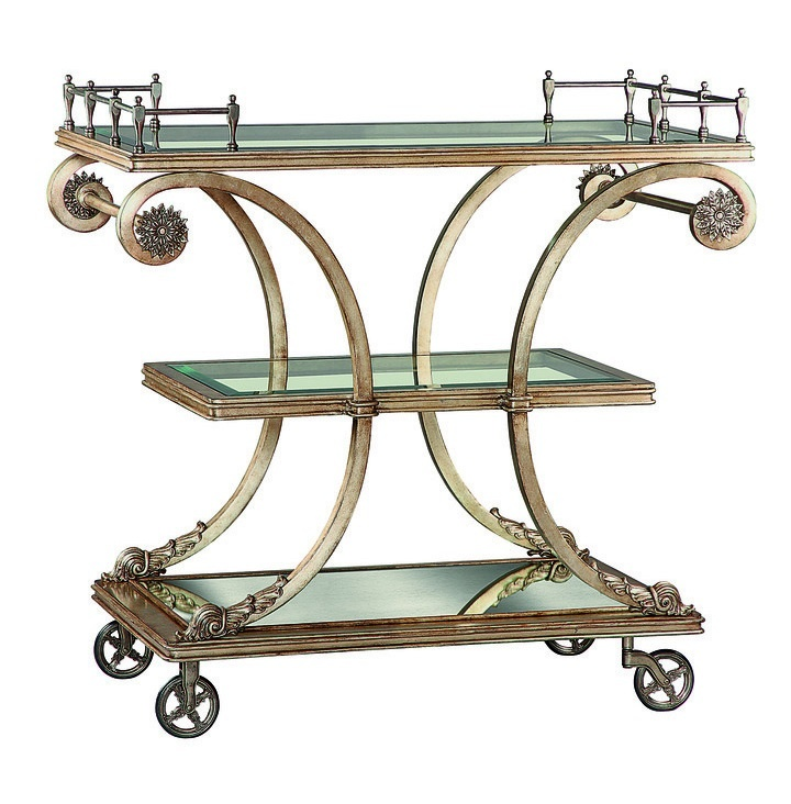 Rivoli Serving Cartshown with:Heirloom BrentwoodfinishAged Gold Leaffinish trimDecorative metalwork in Aged Metal finish withAged Gold Leaf trimInset clear glass top and shelf with beveled edgeAntique Brass gallery and wheels